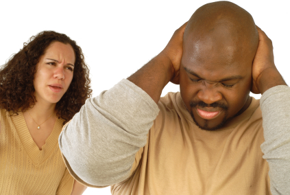 Man shutting his ears and not listening to the persistent yelling of his spouse